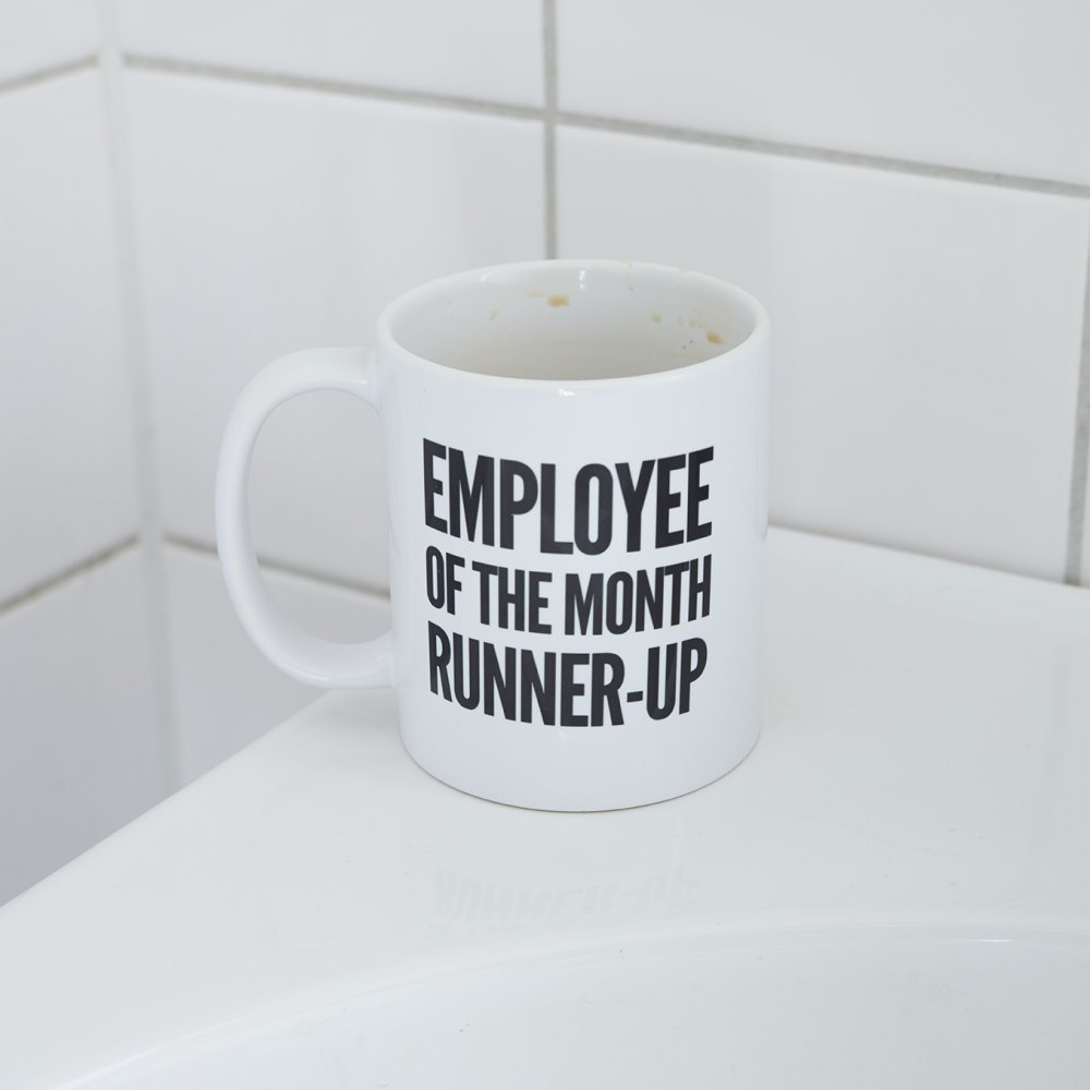 "En mugg med texten ""Employee of the month runner-up"" står på kanten av ett handfat"